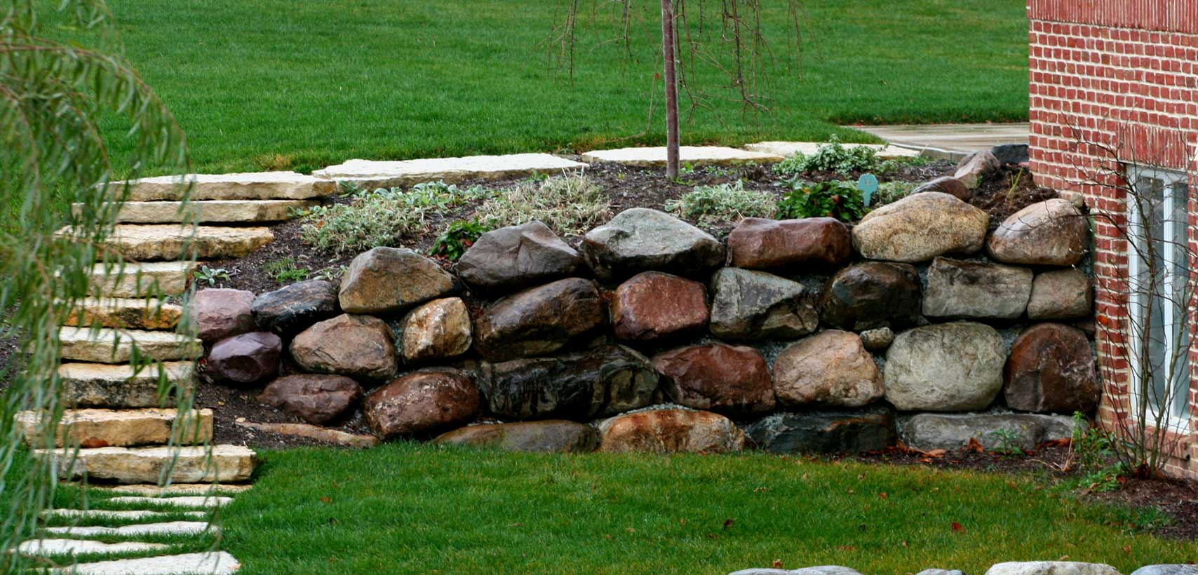 Retaining wall in landscape featuring Glacial Granite boulders from Green Stone | Noblesville and Indianapolis, Indiana